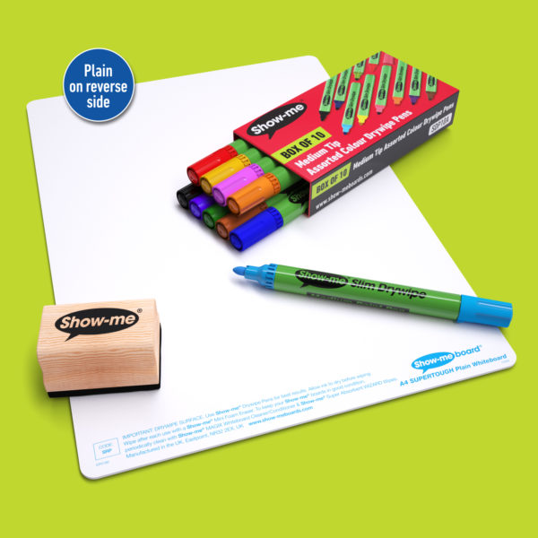Show-me SUPERTOUGH Whiteboard for homeschooling laid on a green background with 10 assorted colour Show-me Pens and a wooden-handled eraser